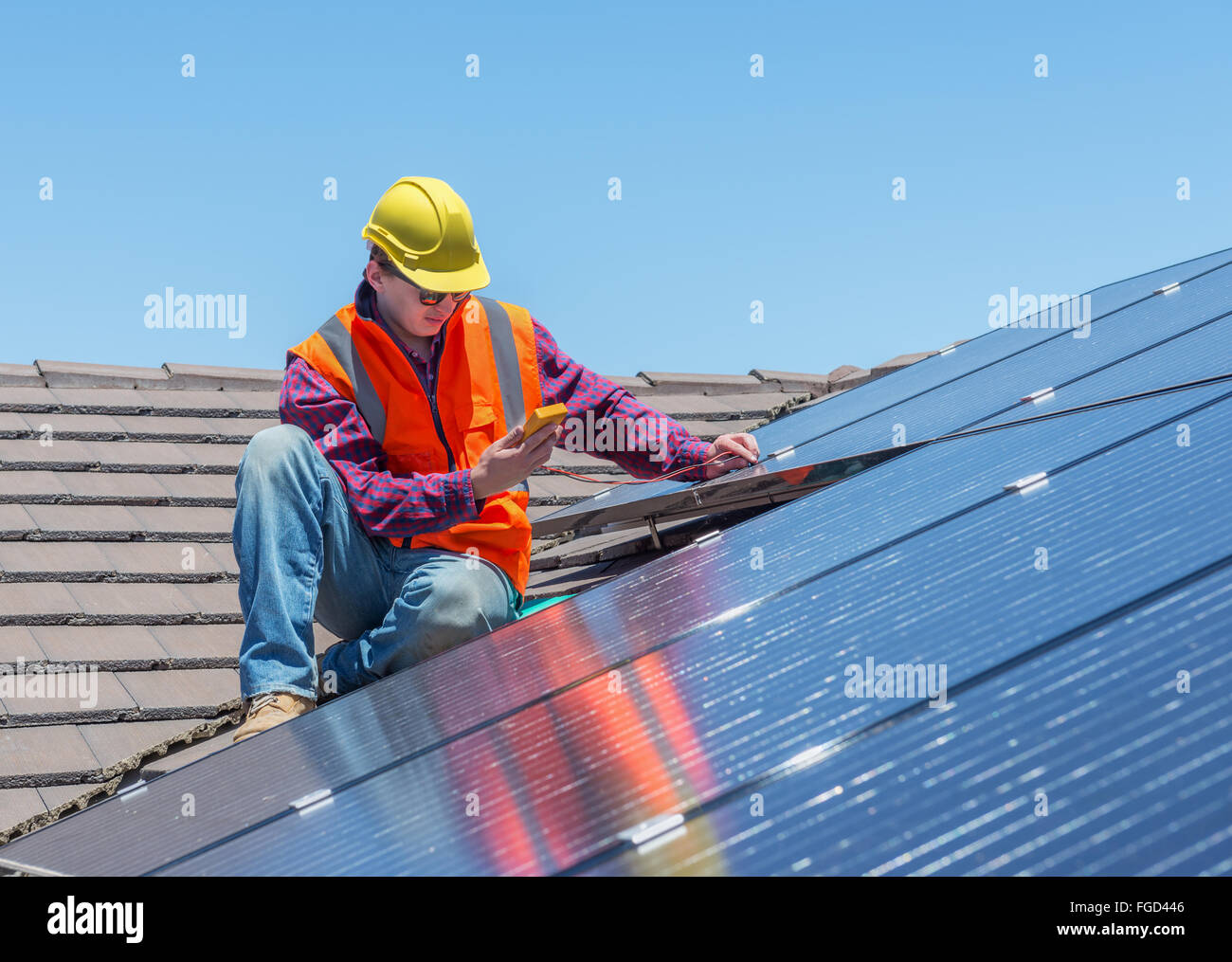 young worker checking solar panels on house roof - Stock Image