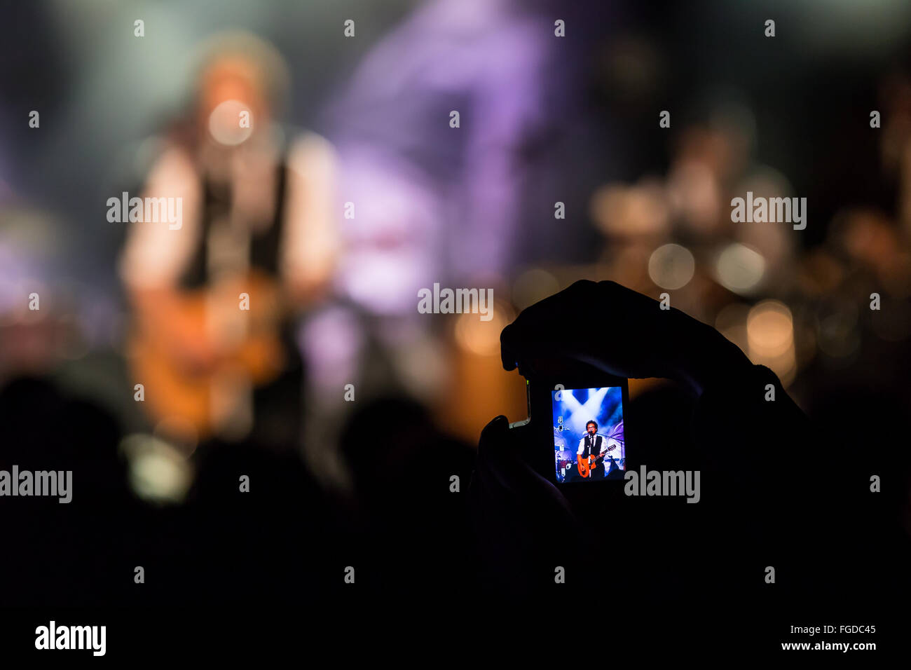 Concertgoers takes a photo with iPhone - Stock Image