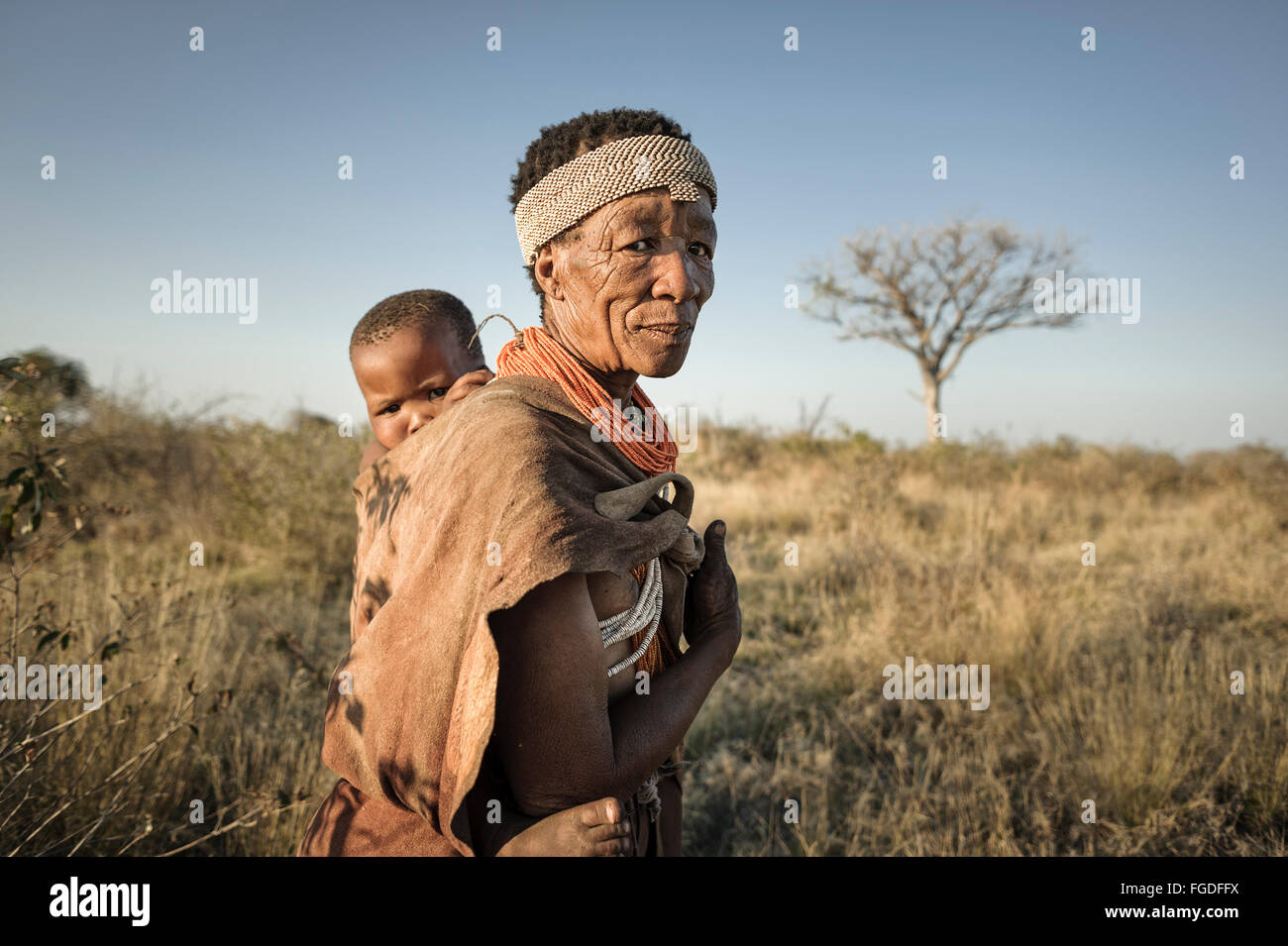 Bushmen woman carrying child at her back - Stock Image
