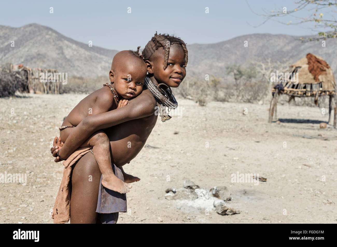 Himba child carrying her sister on her back around their remote village. - Stock Image