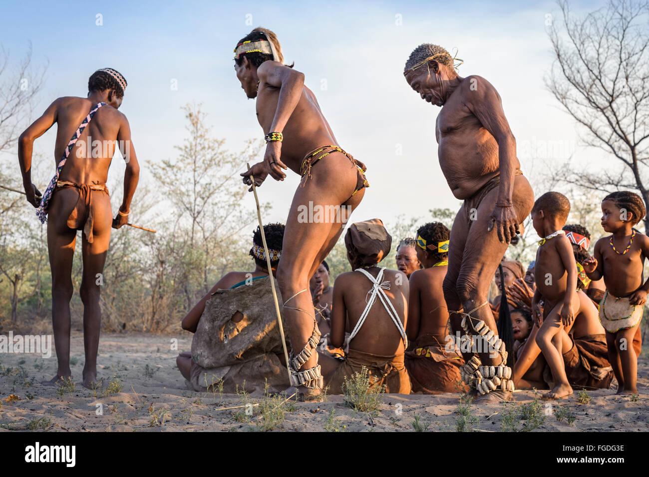 Kalahari San people dancing in circles around people sitting down on the ground and singing. Stock Photo