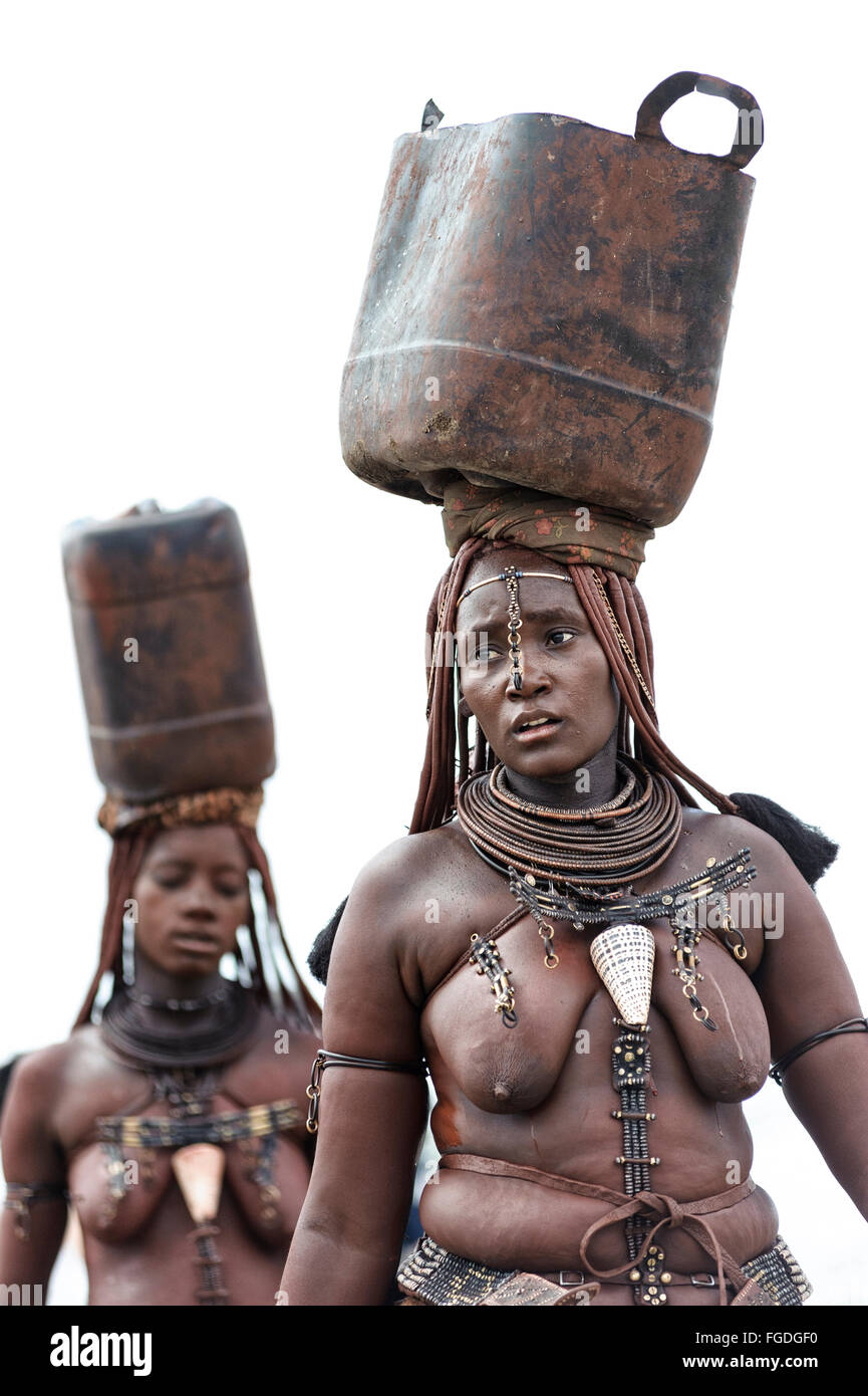 Himba women carrying plastic containers full of water on their heads ...