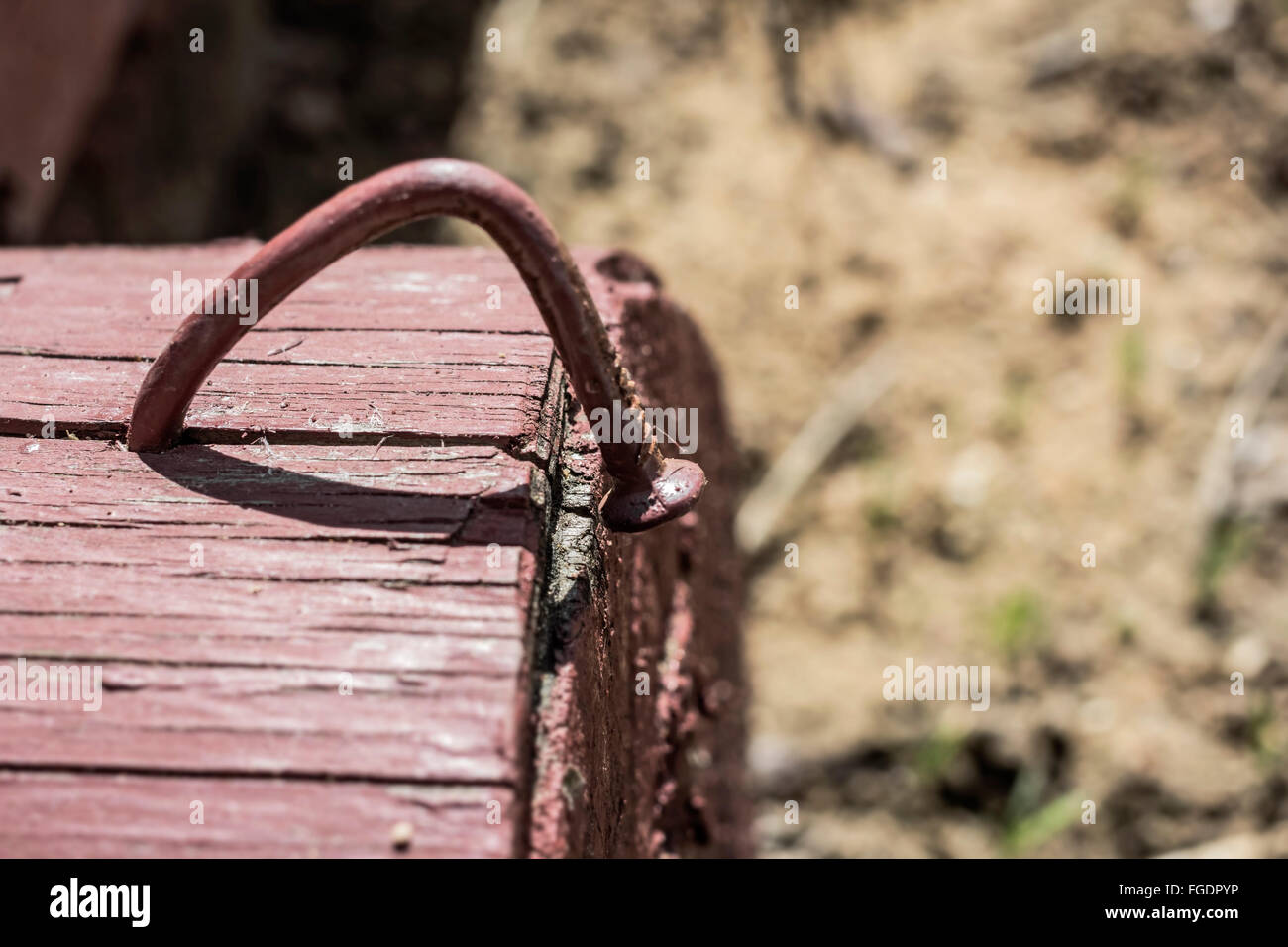 Bent nail driven into block of wood on sunny day - Stock Image
