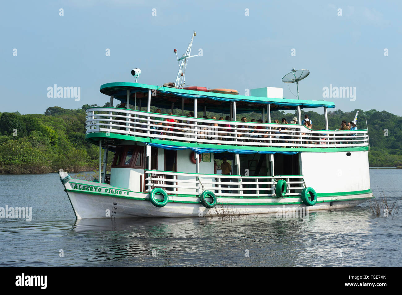 Traditional wood boat navigating with tourists on the Rio Negro, Manaus, Amazona state, Brazil - Stock Image