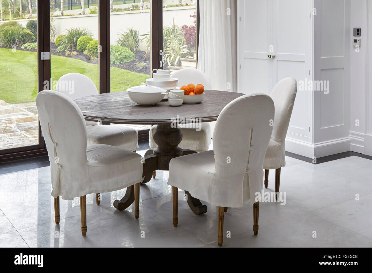 Kitchen Dining Table By Window. Tudor Hall, Potters Bar, United Kingdom.  Architect: Oro Bianco Interior Design Ltd, 2015.
