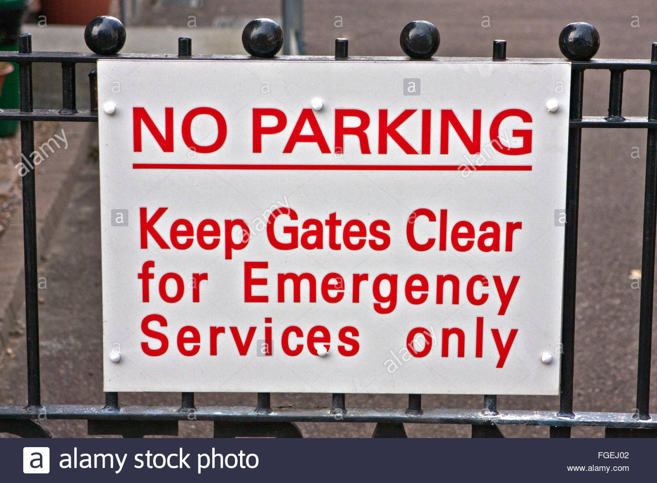 White and red sign on a black wrought iron gate: NO PARKING Keep Gates Clear for Emergency Services only - Stock Image