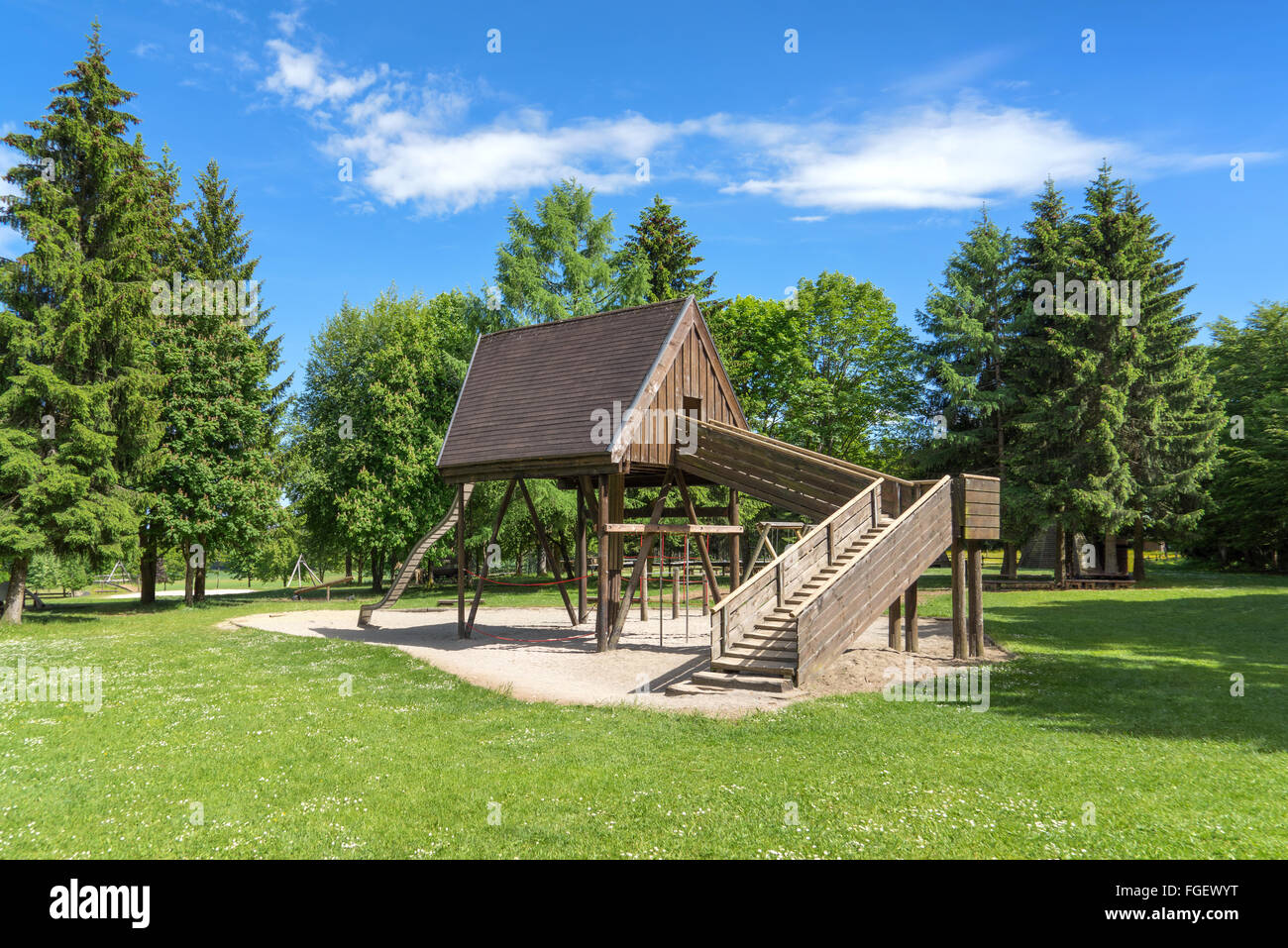 Deserted playground with wooden house on a glade in the forest. Taken on the Rossberg above Albstadt, Swabian Alps, - Stock Image
