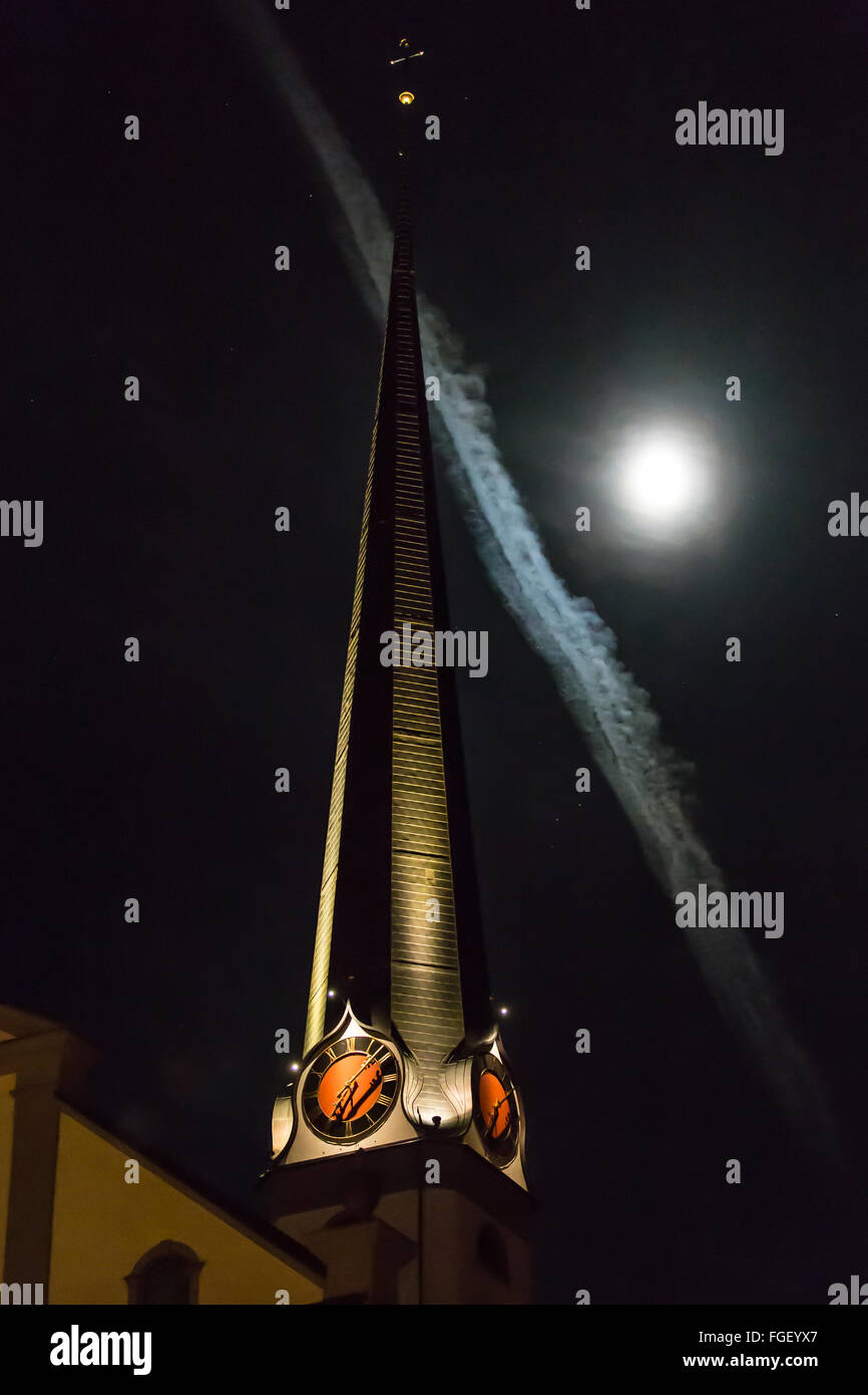 Church tower with moon and contrails - Stock Image