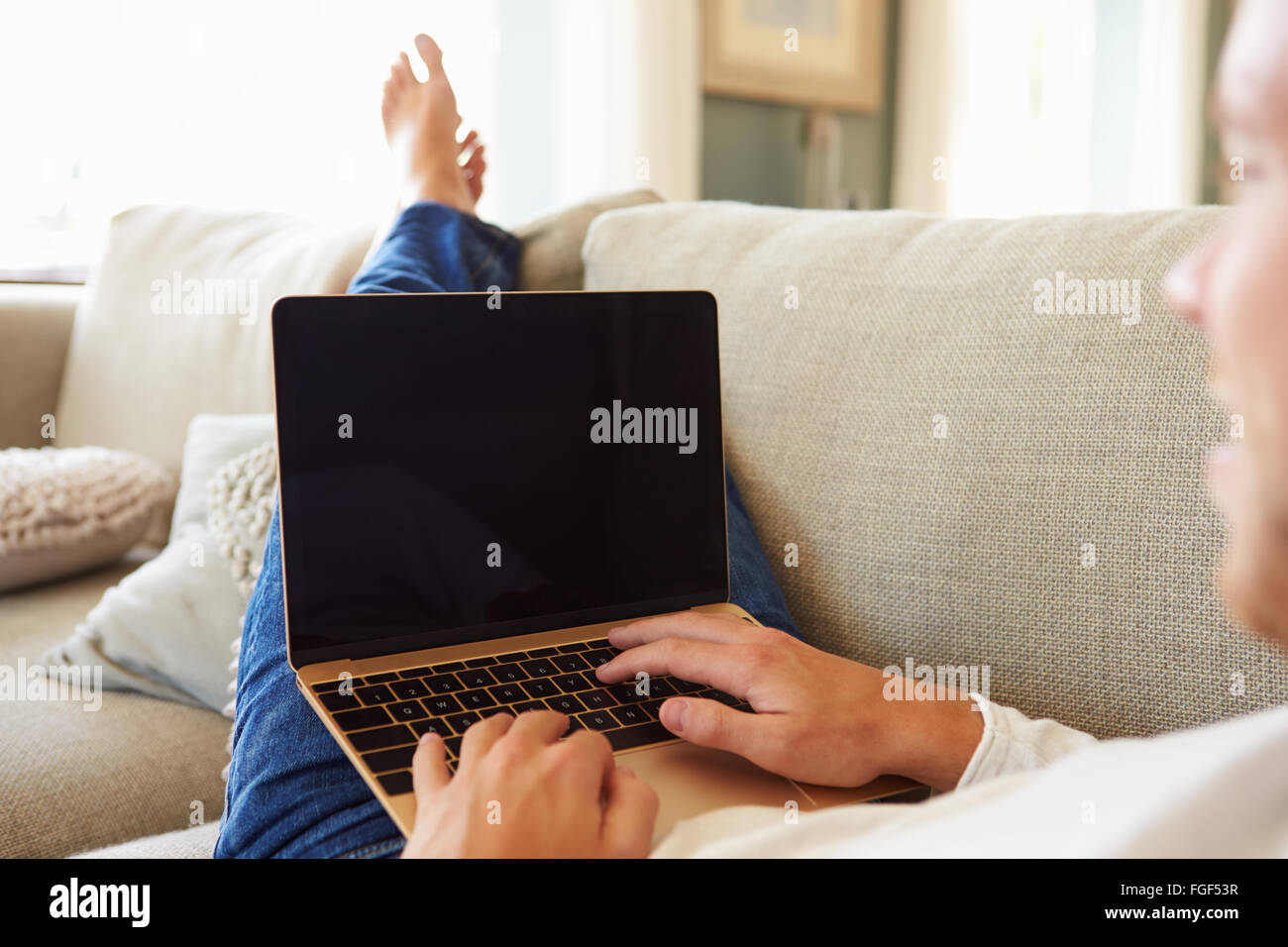 Man Relaxing On Sofa At Home Using Laptop Computer - Stock Image