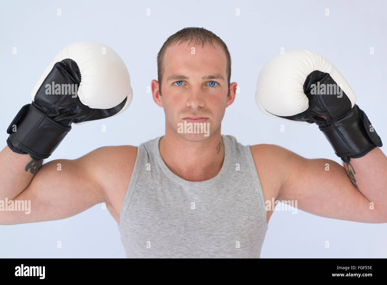 Man wearing boxing gloves flexing his biceps with a serious expression of concentration - Stock Image