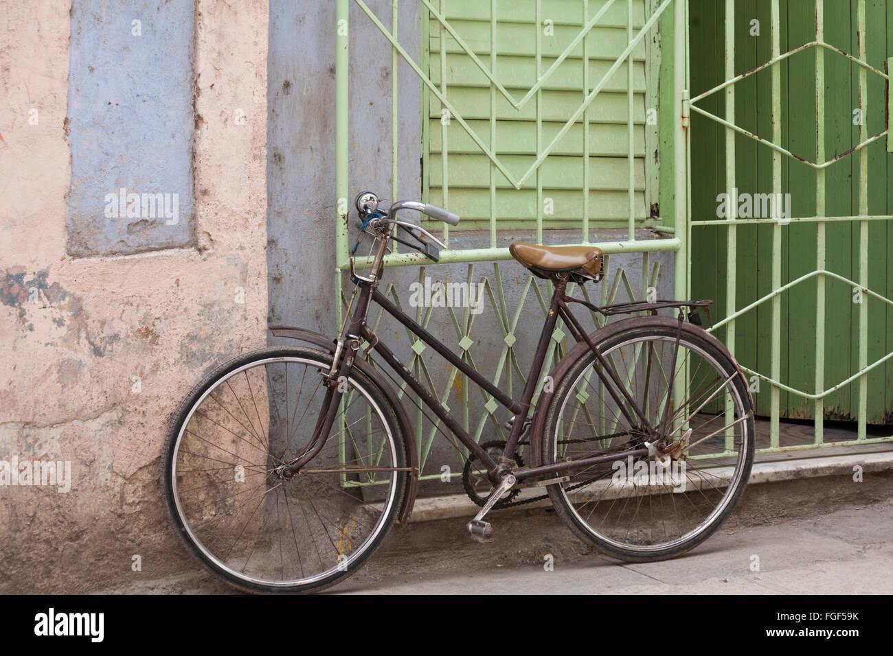 Daily life in Cuba - bicycle bike leant against green wrought iron metal railings at Havana, Cuba, West Indies, - Stock Image