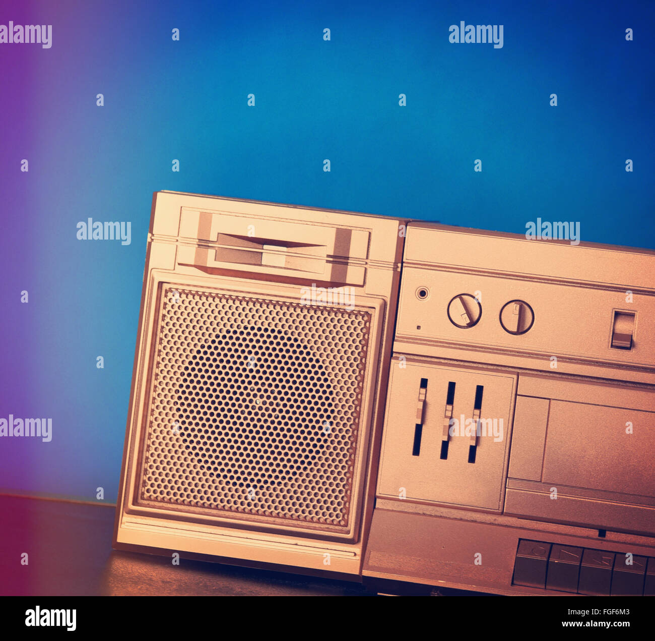A closeup or a speaker of a retro gold boombox eighties stereo with a blue background for a music or sound concept. - Stock Image