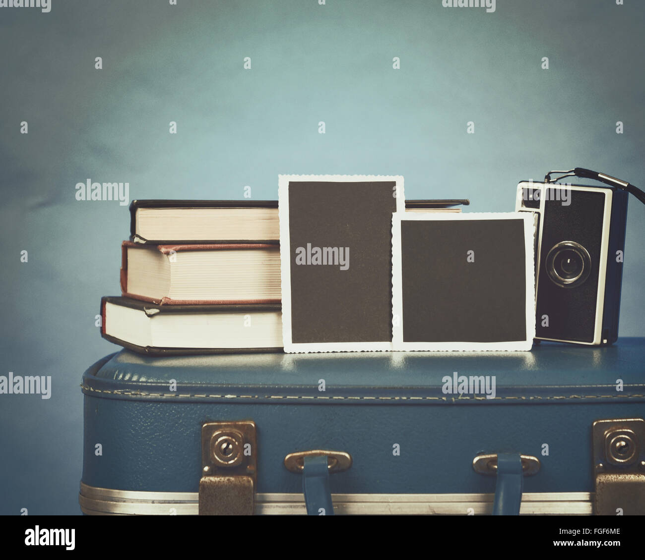 Old photographs, a camera and books are on top of a vintage suitcase with a blue background for a memory concept - Stock Image