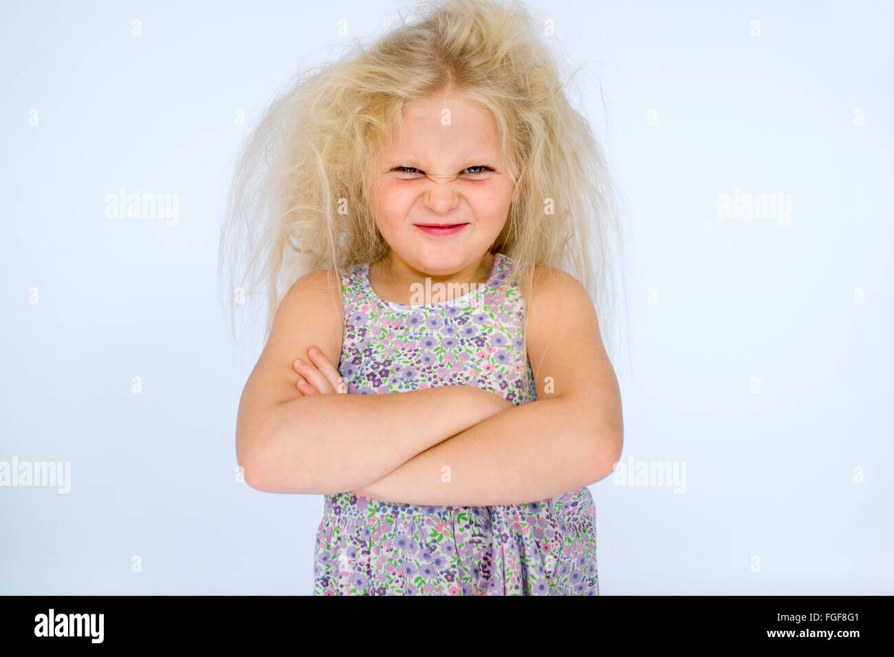 Young girl with messy blonde hair frowning with folded arms and a cheeky grin Stock Photo