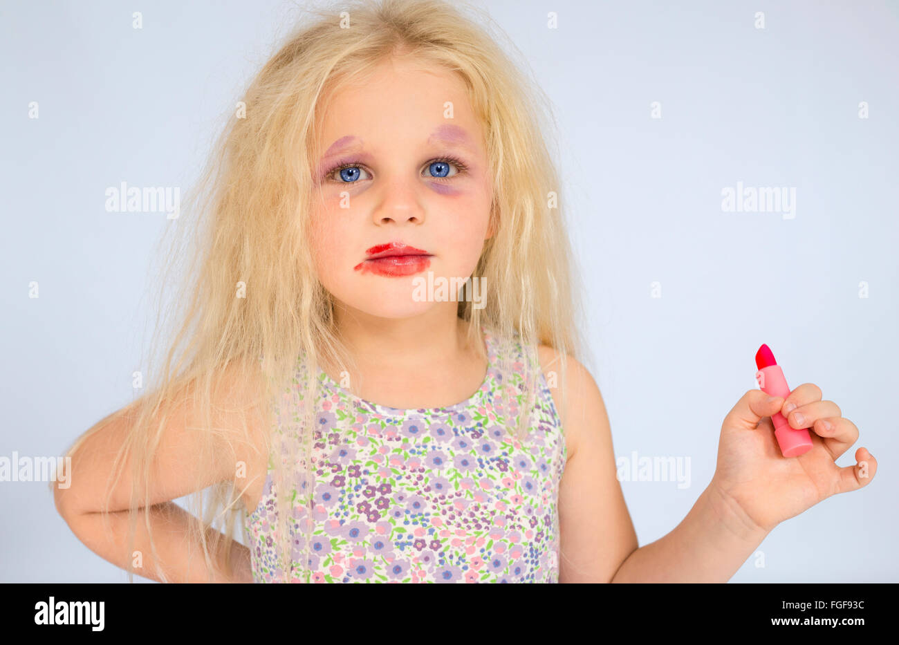 Young girl with blonde hair wearing smudged make up holding a red lipstick - Stock Image