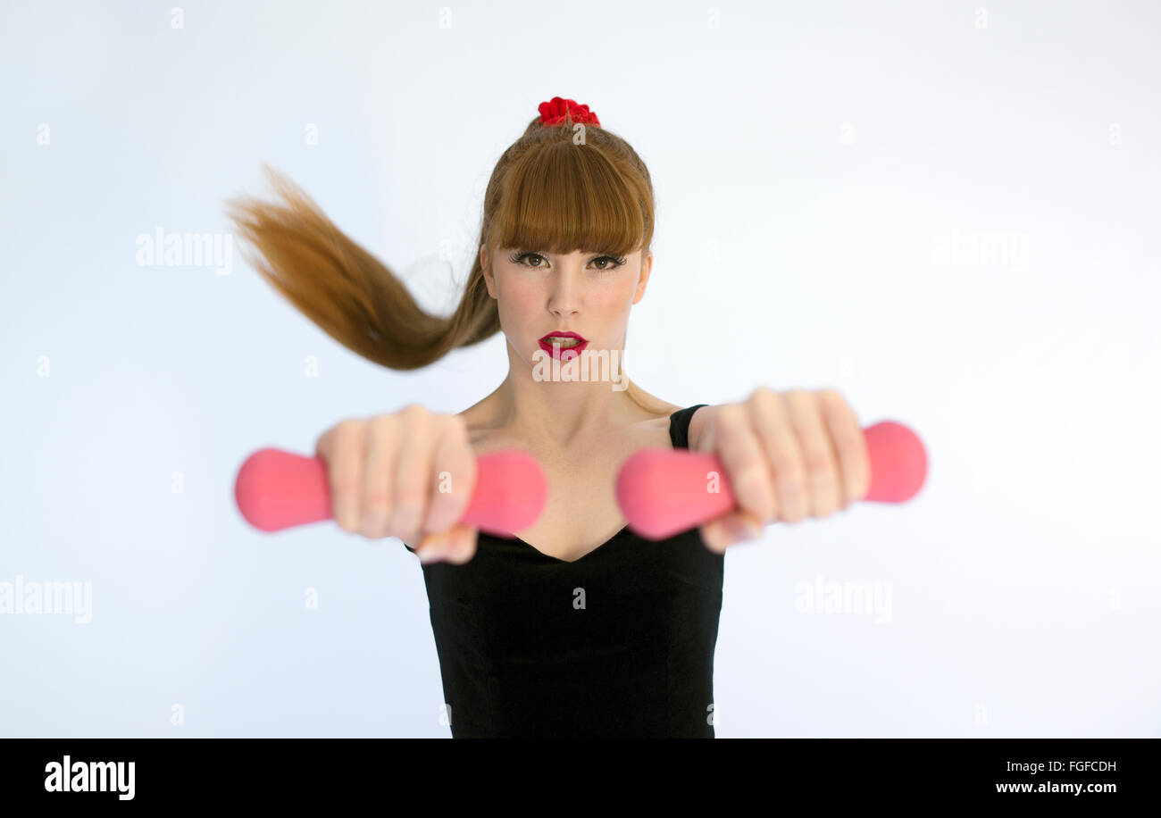 Woman with long brown hair wearing a sweat headband holding pink dumbbells exercising - Stock Image