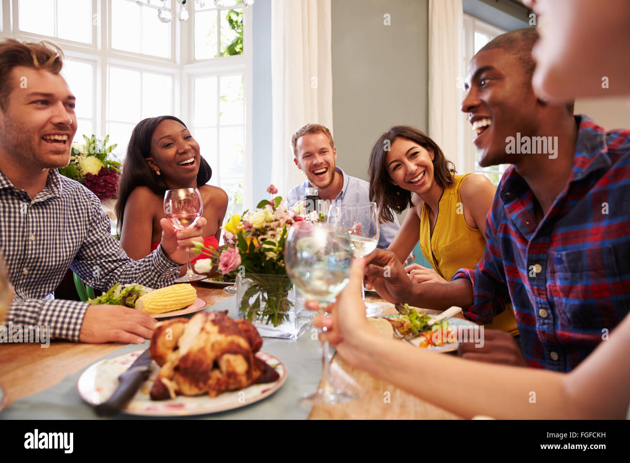 friends at home sitting around table for dinner party stock photo
