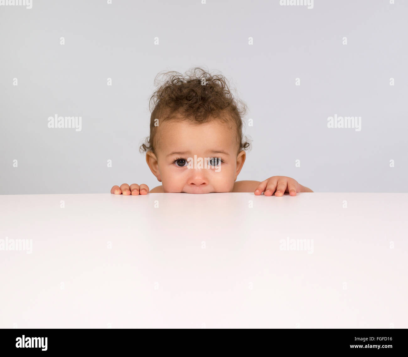 Cute baby boy peeping over a table top - Stock Image