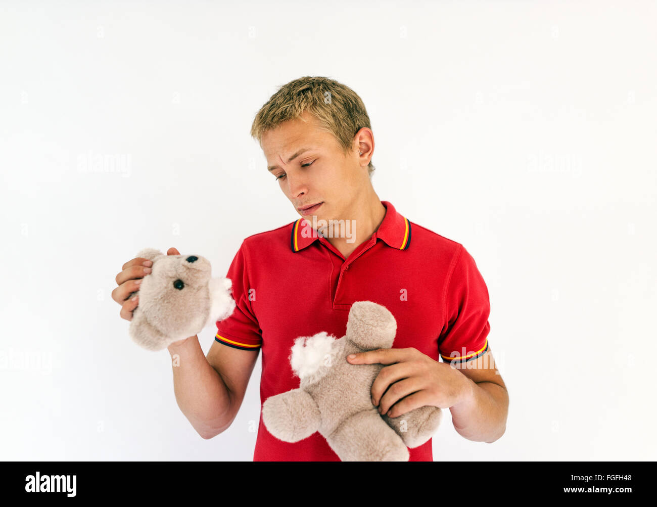 Man holding the head and body of a cute toy teddy bear looking sad - Stock Image
