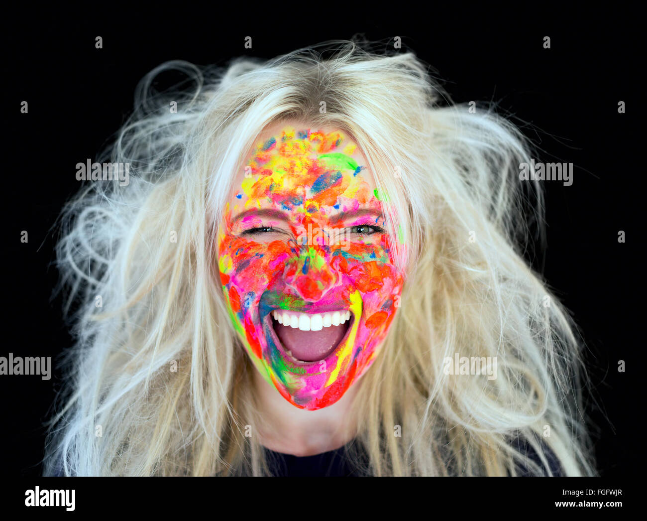 Woman with messy blonde hair with face covered in multi coloured paint laughing Stock Photo