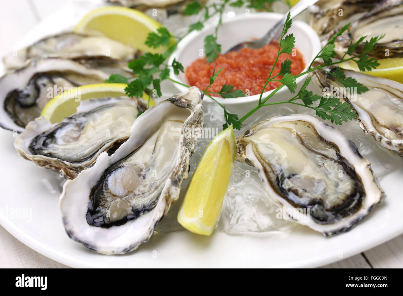 fresh oysters plate isolated on white wooden background Stock Photo
