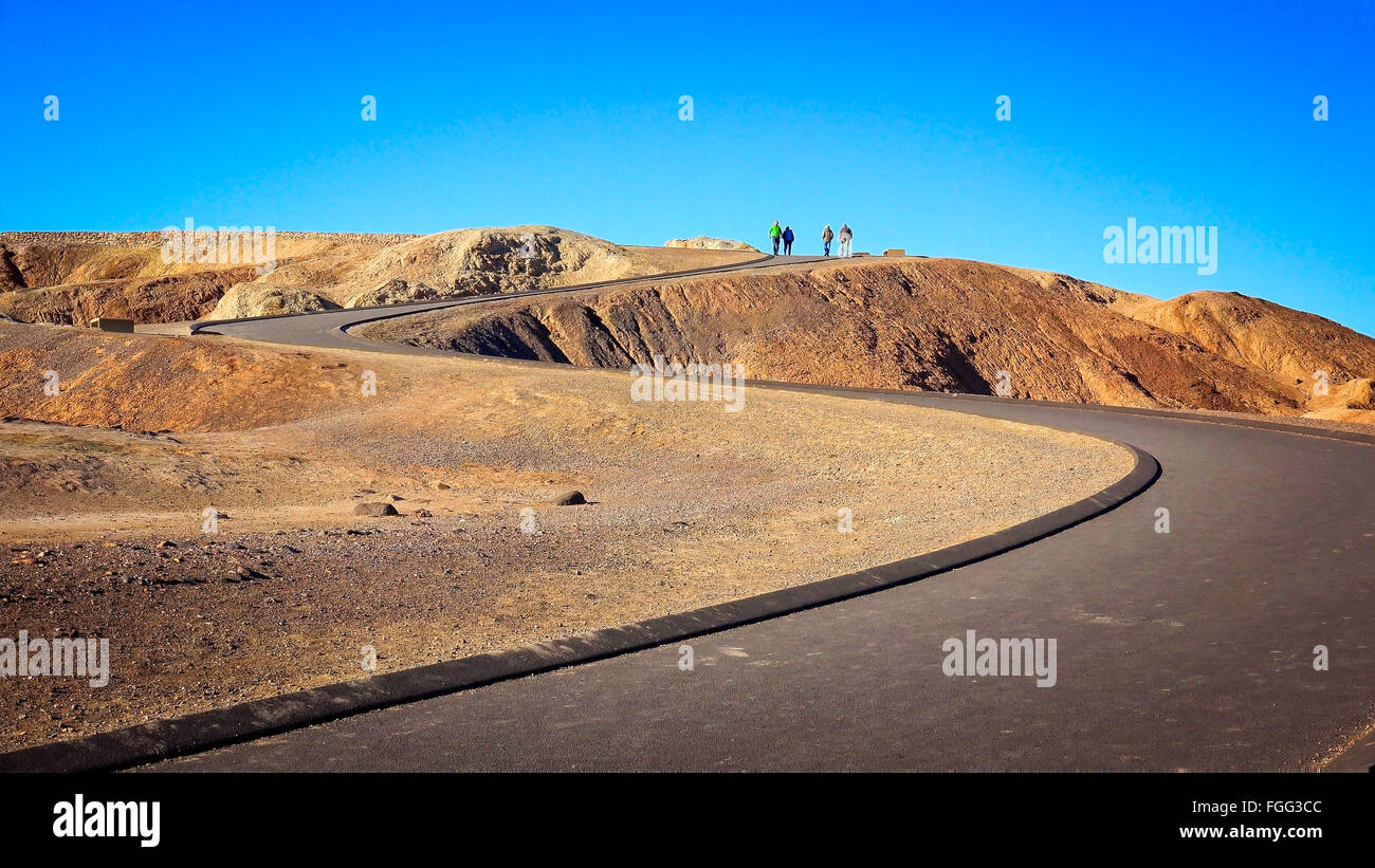 Visitors at the top of a winding path leading to Zabriskie Point in Death Valley National Park - Stock Image