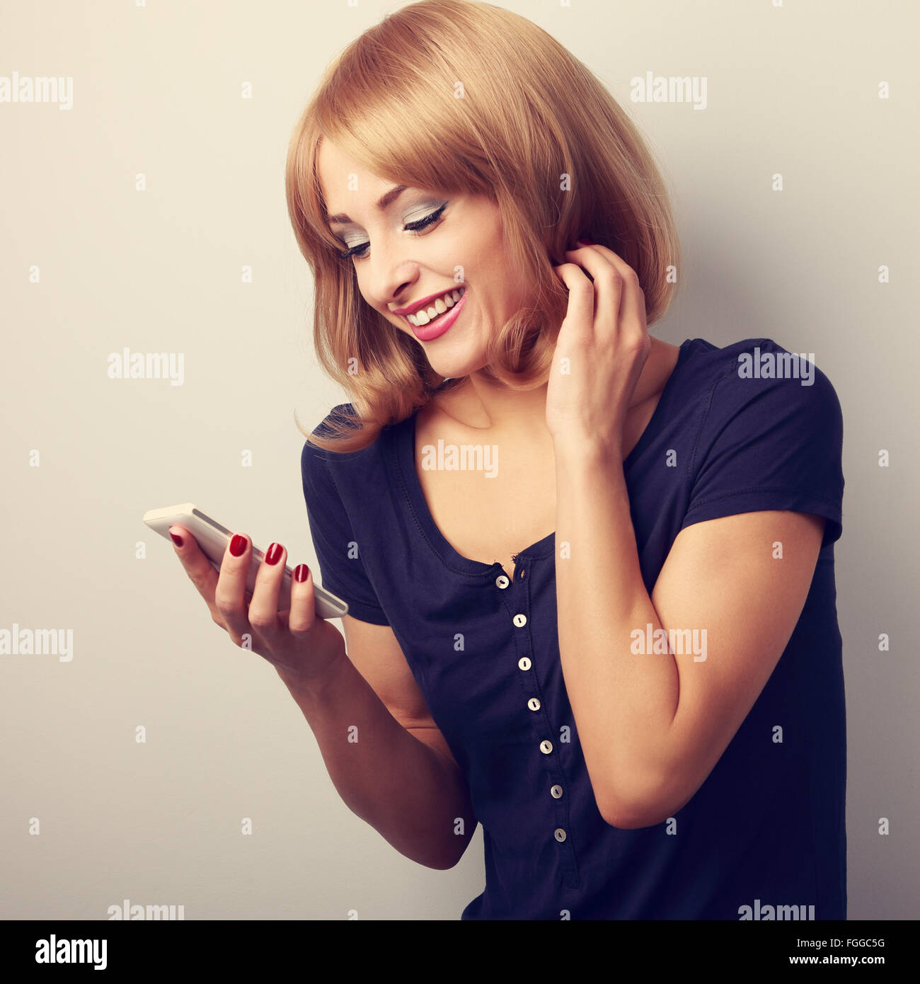 Happy smiling blond woman reading sms in mobile phone. Toned closeup portrait - Stock Image