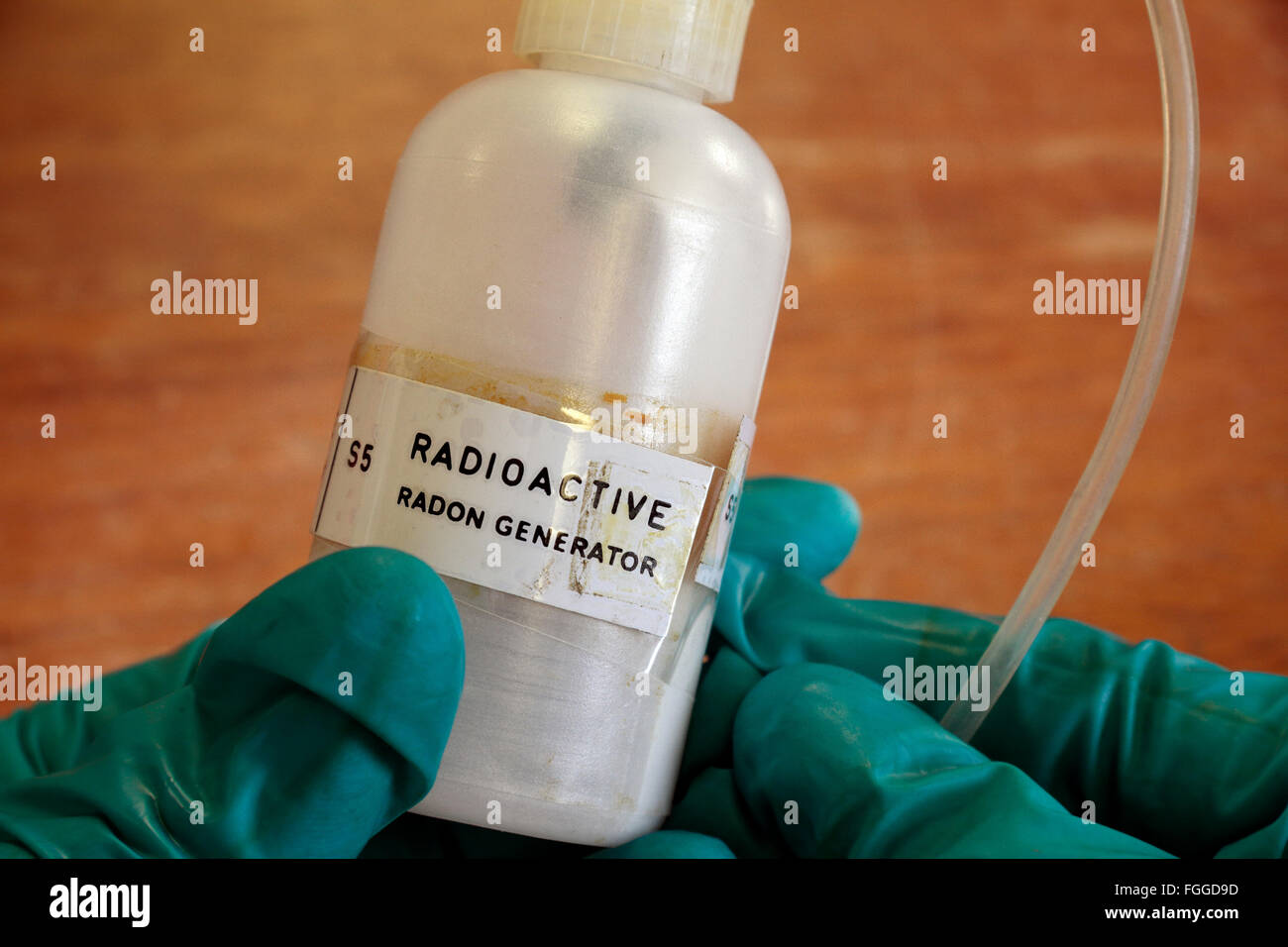 A UK high school radioactive radon 220 generator being held in a gloved hand above a table. - Stock Image