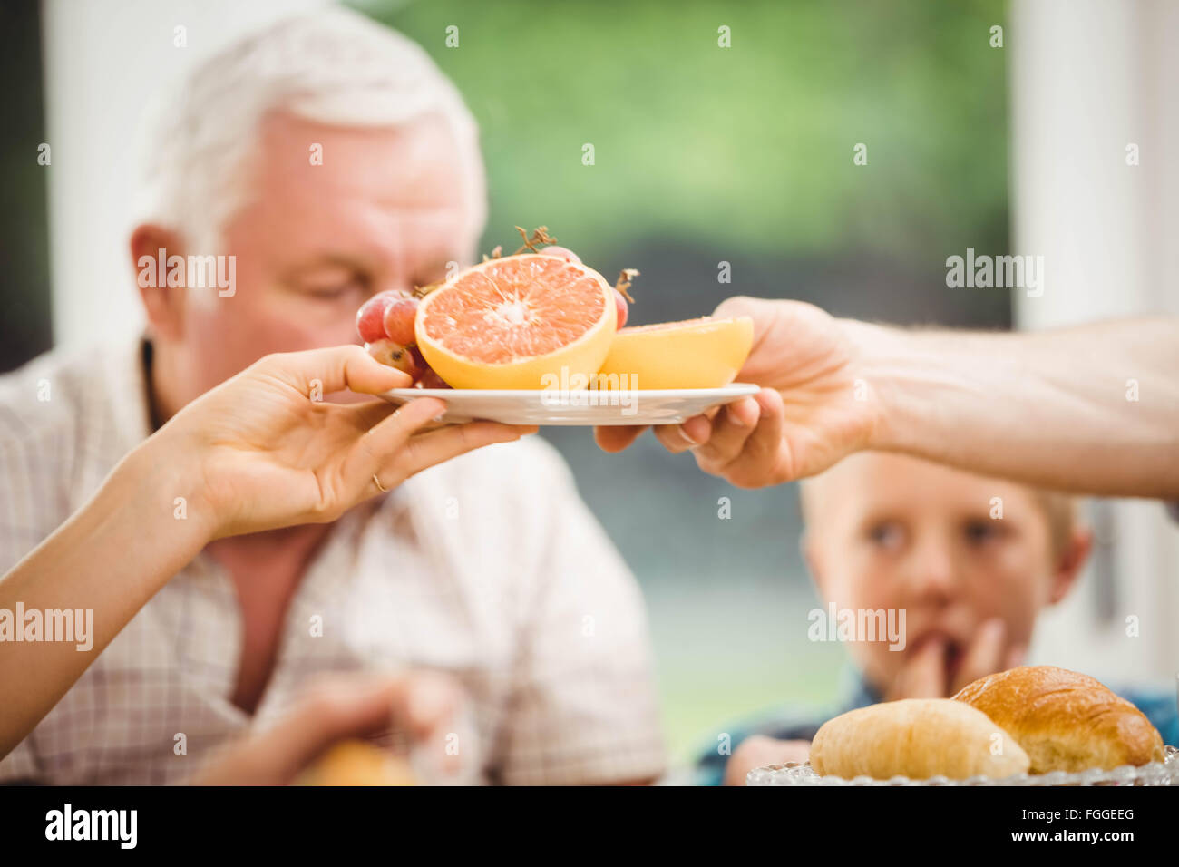 Close-up of hands passing plate of fruits - Stock Image