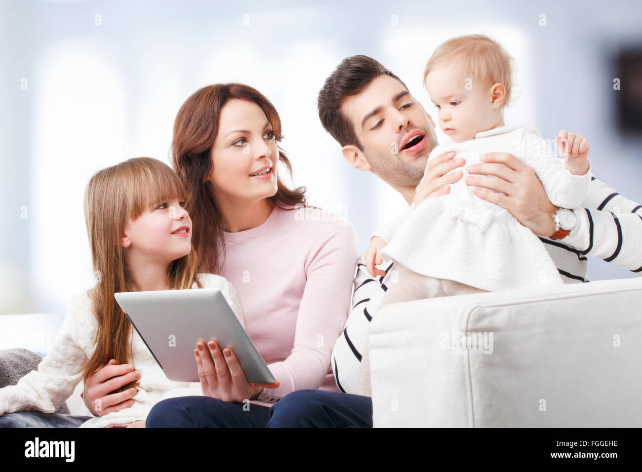 Portait of happy family sitting at sofa at living room while having fun. - Stock Image