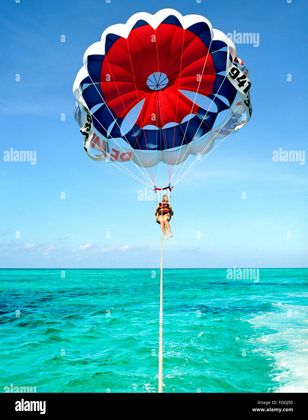 A foreign tourist parasails off of Grace Bay Beach, Providenciales, Turks and Caicos, British West Indies. - Stock Image