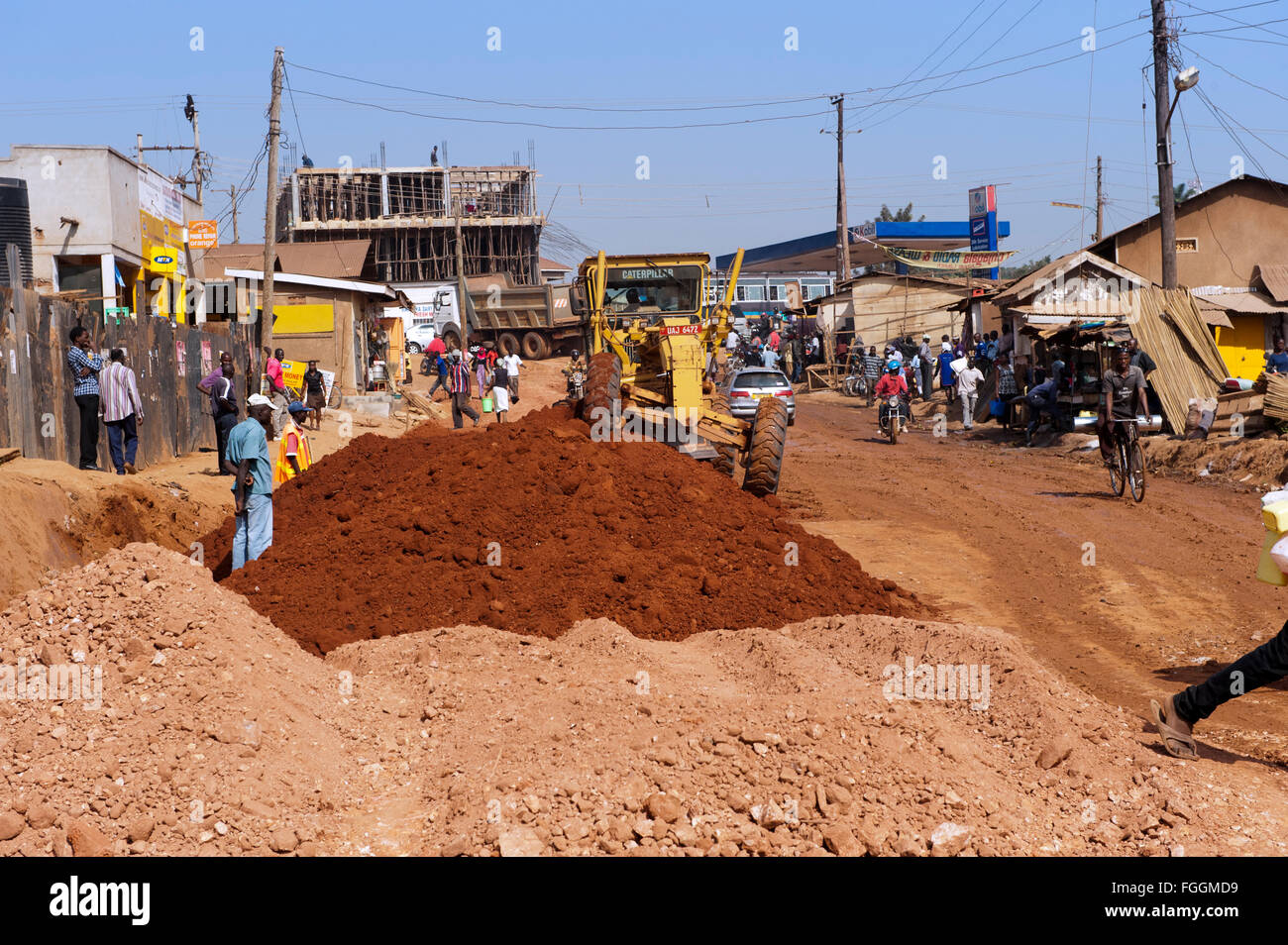 Street repairs in Ugandan town, as large earth movers mend a stretch of road. - Stock Image