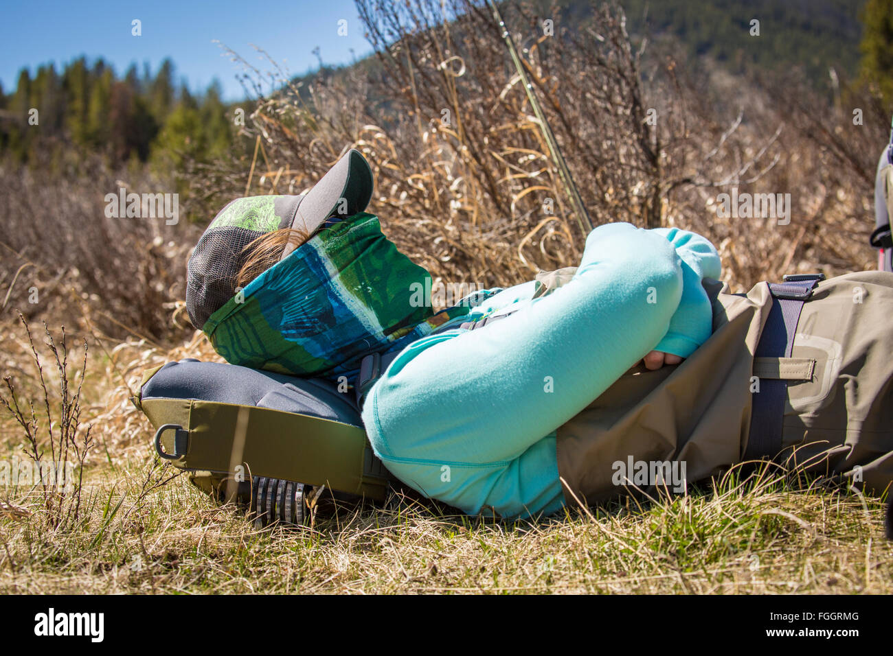 Young woman naps beside the Gallatin River in Montana. - Stock Image