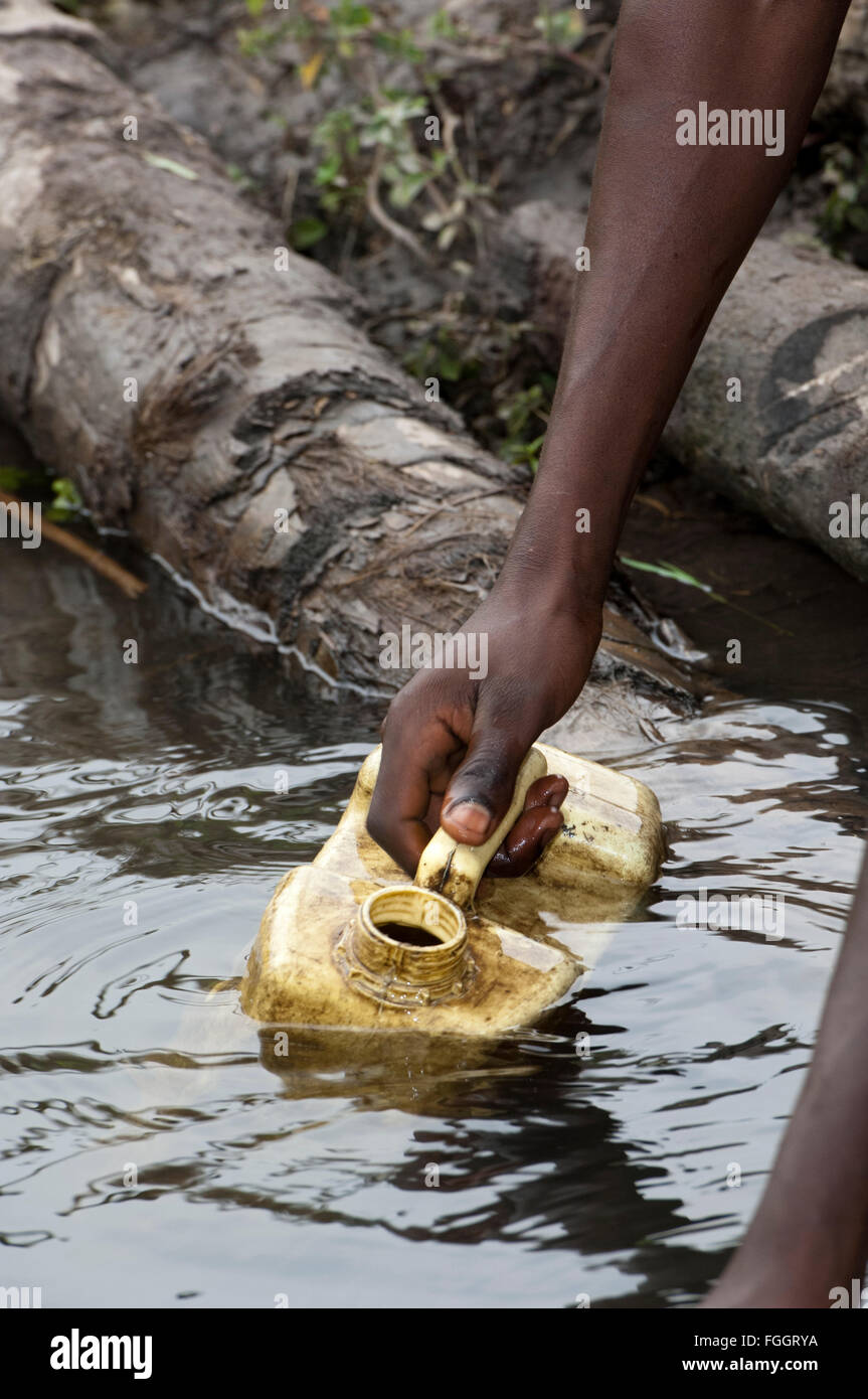 Collecting container of water from a dirty looking pool of water, Uganda. - Stock Image