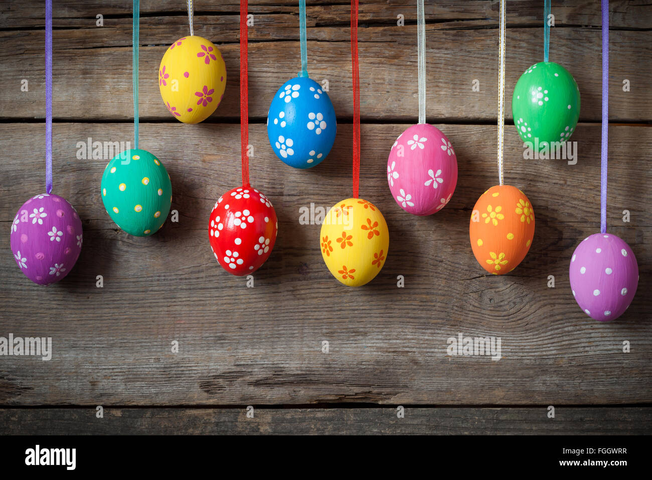 Hanging colorful eggs on rustic wooden background Stock Photo