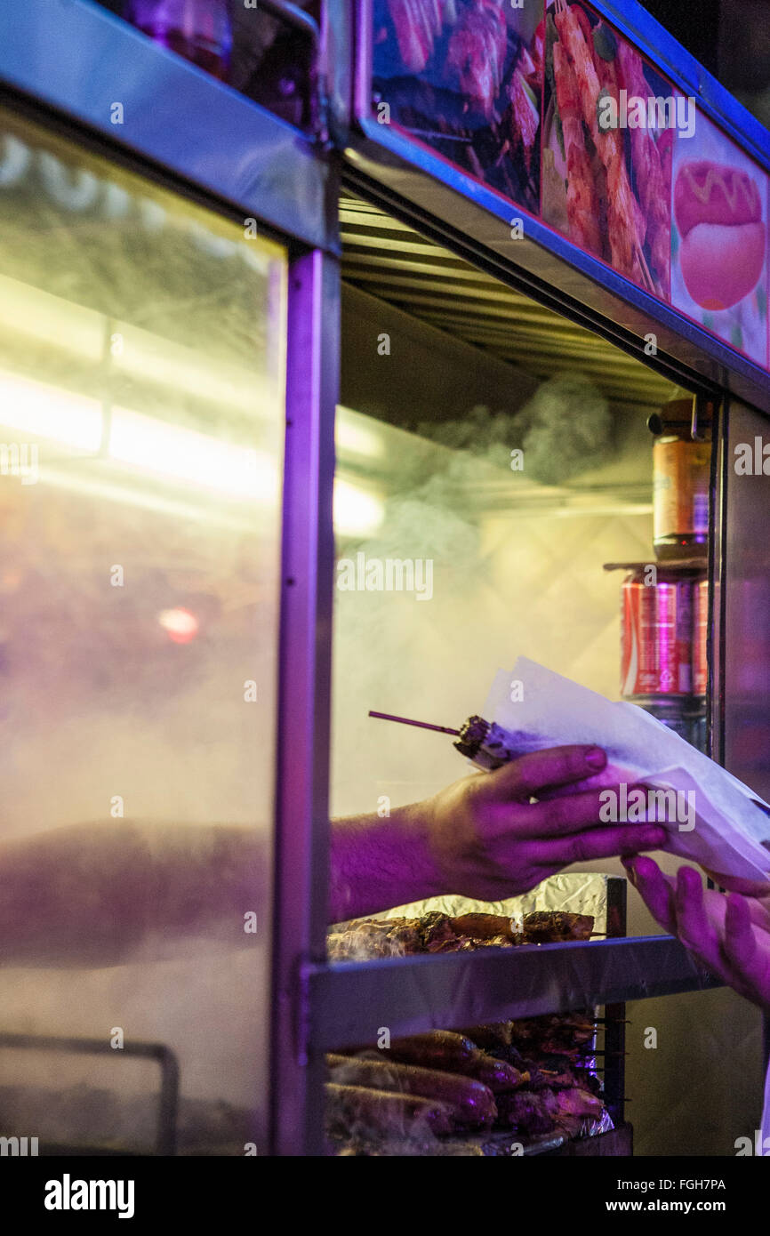 A vendor's hand reaches out of a sidewalk cart in Times Square, handing a shish kebab to customer. - Stock Image