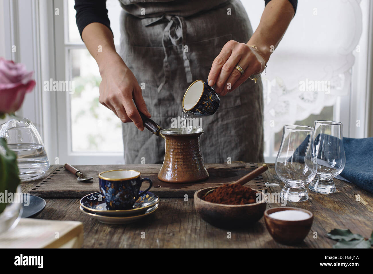 A woman is pouring water into a small pot to make Turkish Coffee. - Stock Image