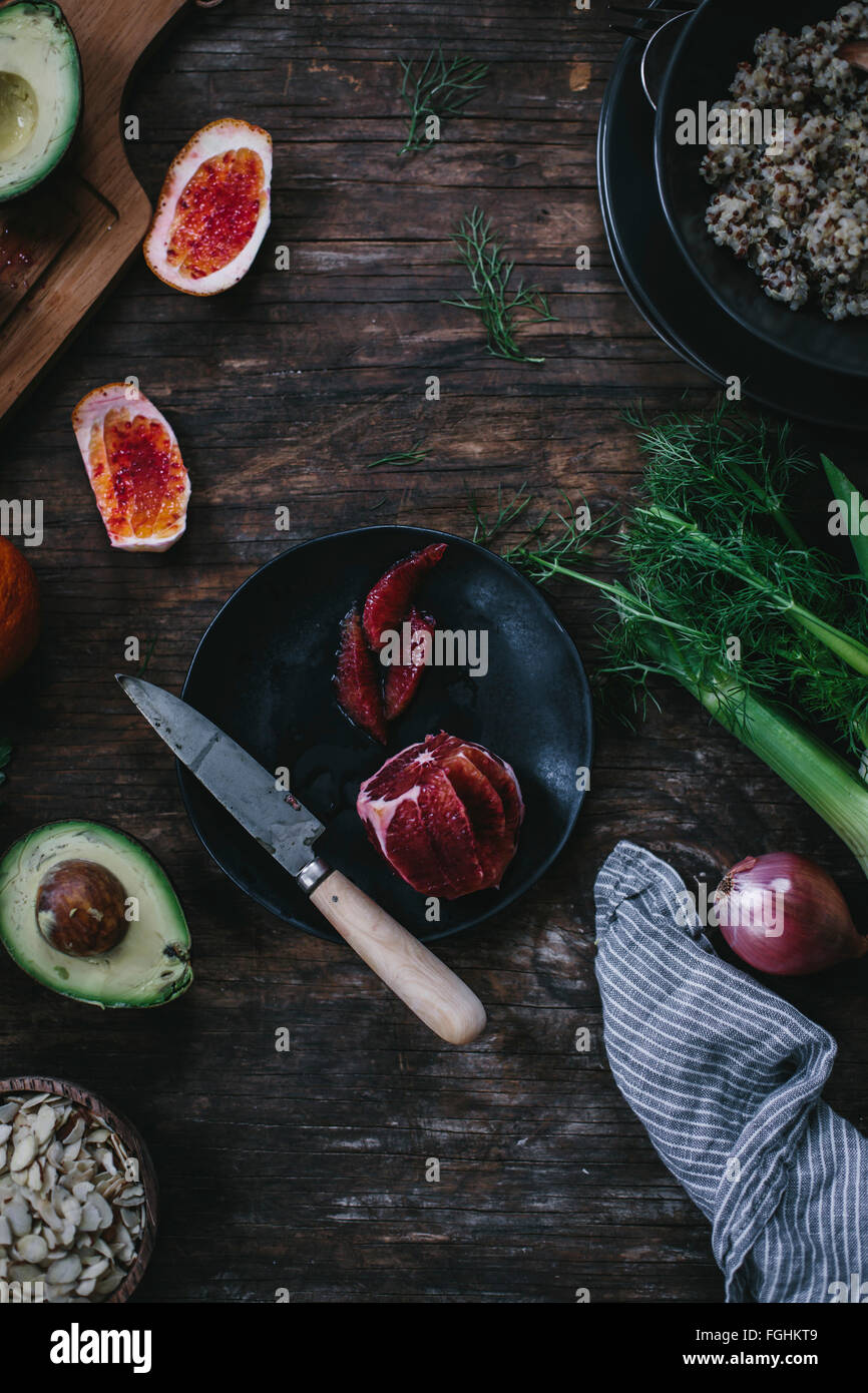 Sliced blood oranges are surrounded with cooked quinoa avocado sliced almonds fennel and a shallot. Photographed - Stock Image