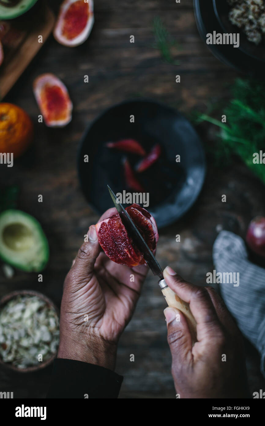 A man is slicing blood oranges photographed from the top. - Stock Image
