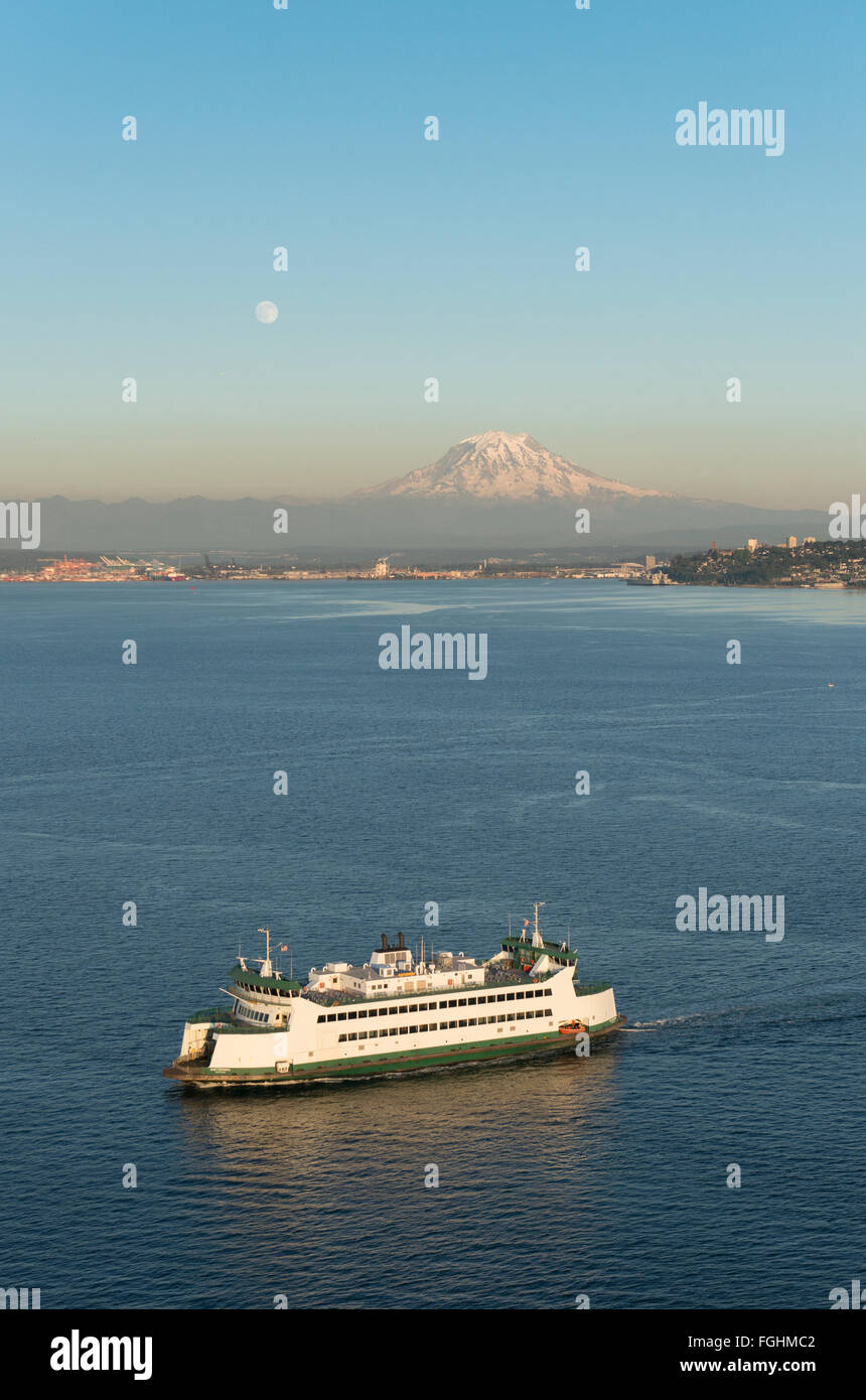 The Washington State Ferry sails in front of Mount Rainier and a full moon at sunset. Stock Photo