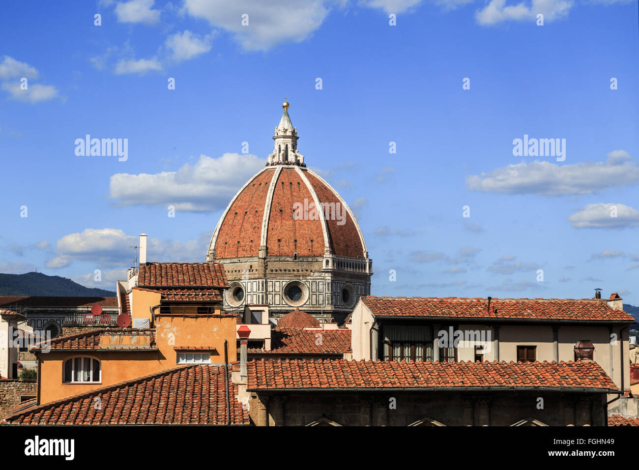 Close up top view of Florence houses with orange roofs and with a big dome, on cloudy blue sky background. - Stock Image