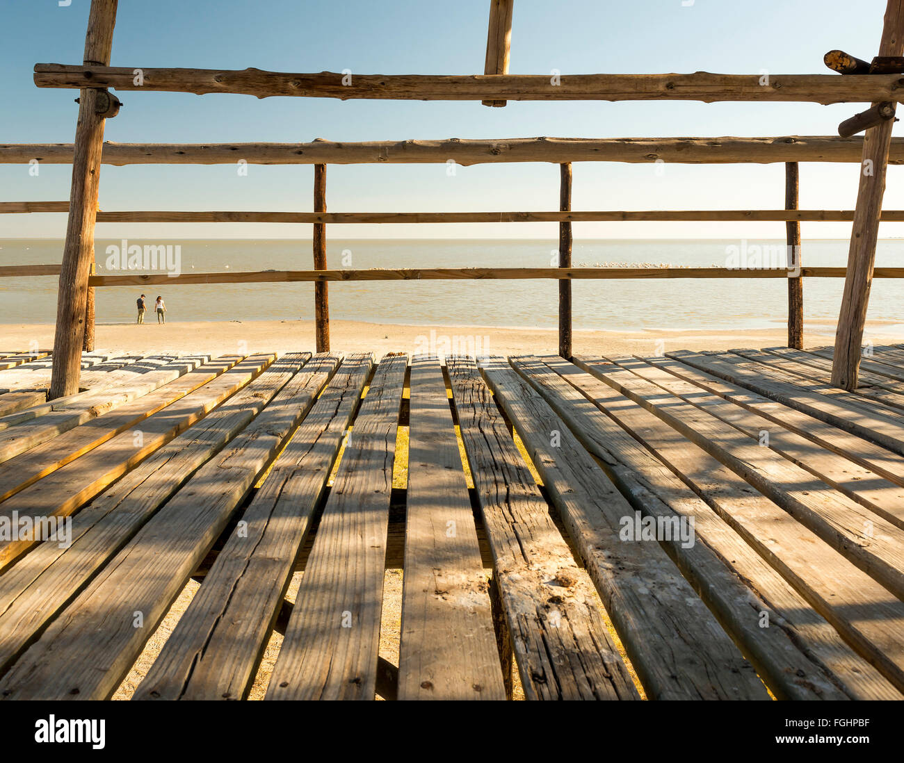 Wooden beach hut looks out over two tourists in the Makgadikgadi Pan in Botswana, Africa - Stock Image