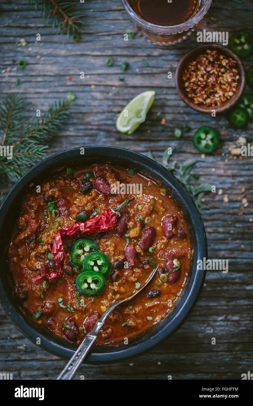 A bowl of turkey and bean chili topped off with slices of jalapeno and a hot dried serrano pepper is photographed - Stock Image