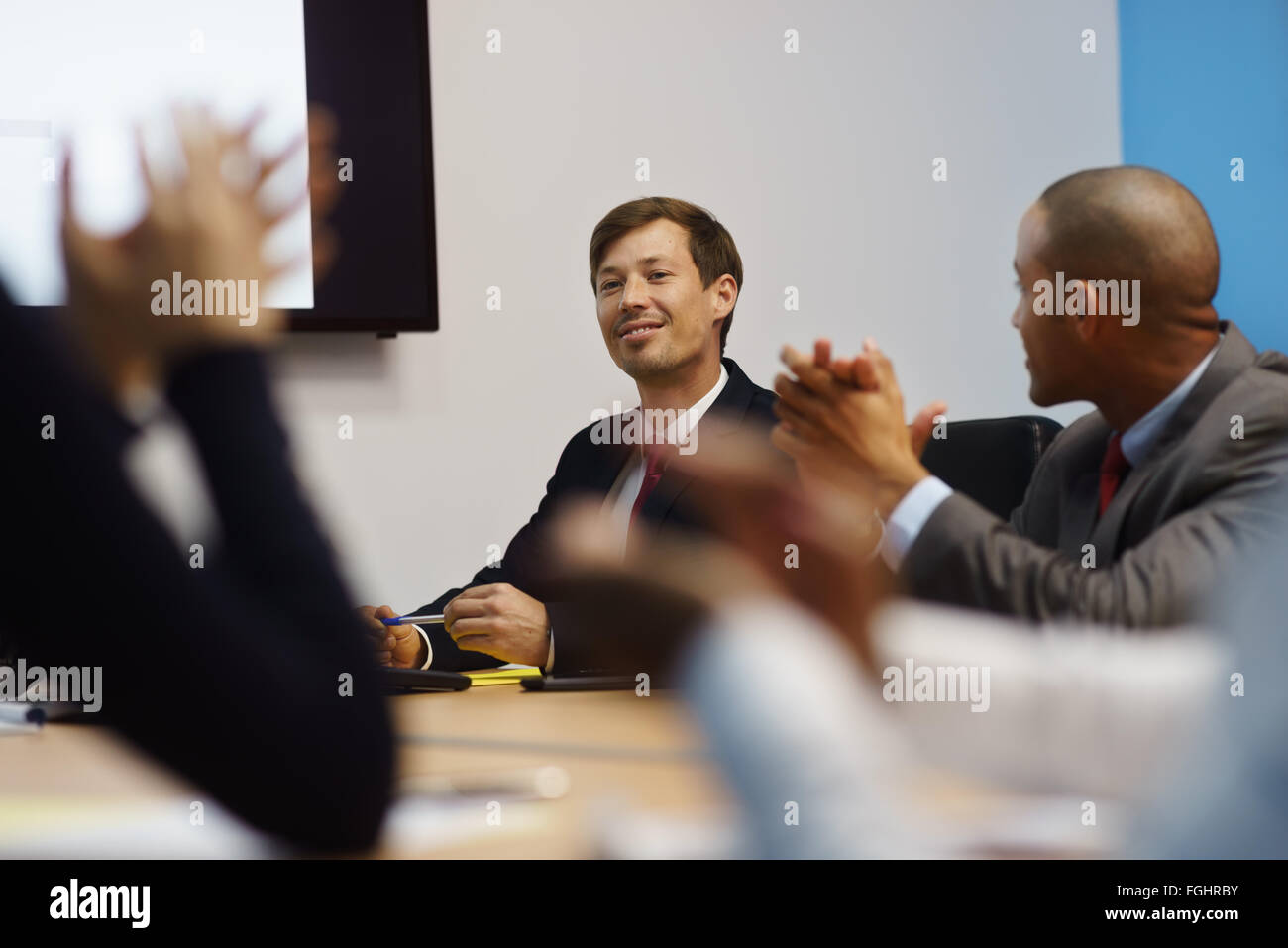 Group of business people meeting in corporate conference room, applauding at a coworker during his presentation. - Stock Image