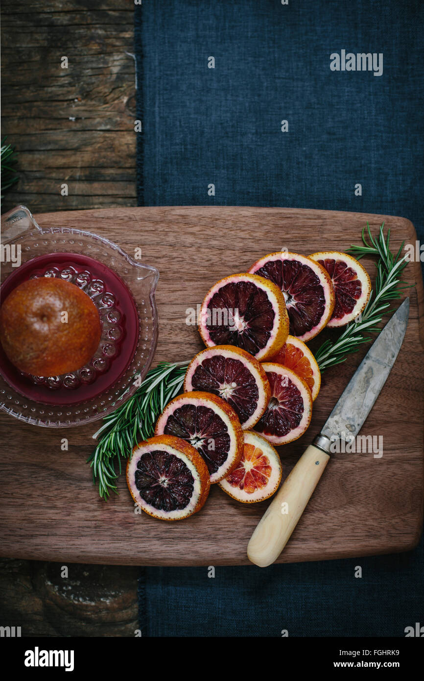 Slices of blood oranges are displayed on a wood word - Stock Image