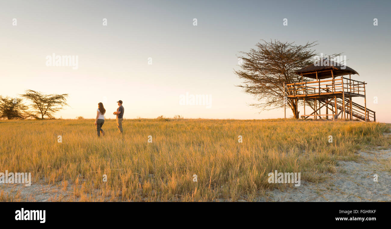 A young couple stand in long grass and watch the sunset while on safari in the Makgadikgadi Pans, Botswana, Africa - Stock Image