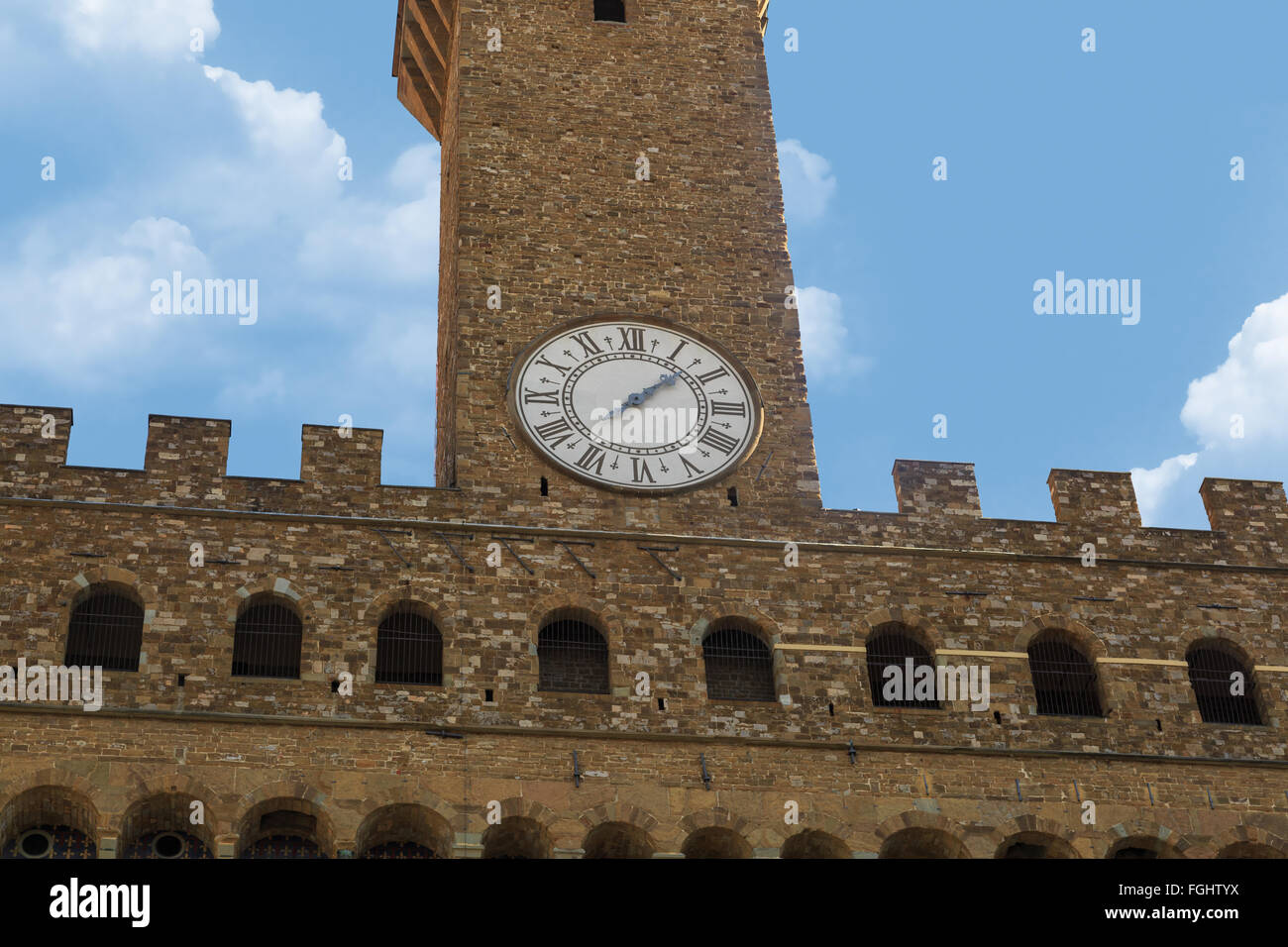 View of historical Vecchio Palace in Piazza Della Signoria in Florence, on cloudy blue sky background. - Stock Image