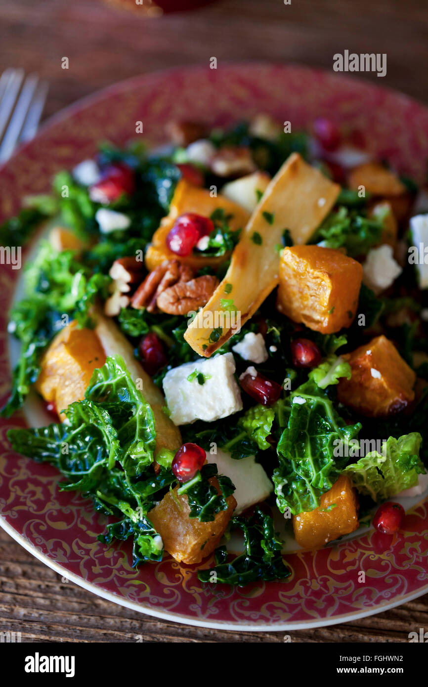 Festive kale roasted sweet potatoes and parsnips salad with Feta cheese pecans and pomegranate in a bowl - Stock Image