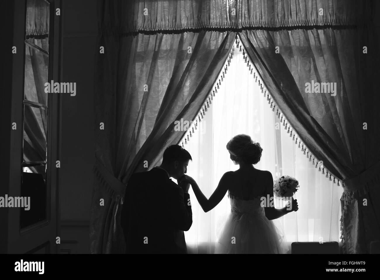 bride and groom standing in front of window Stock Photo
