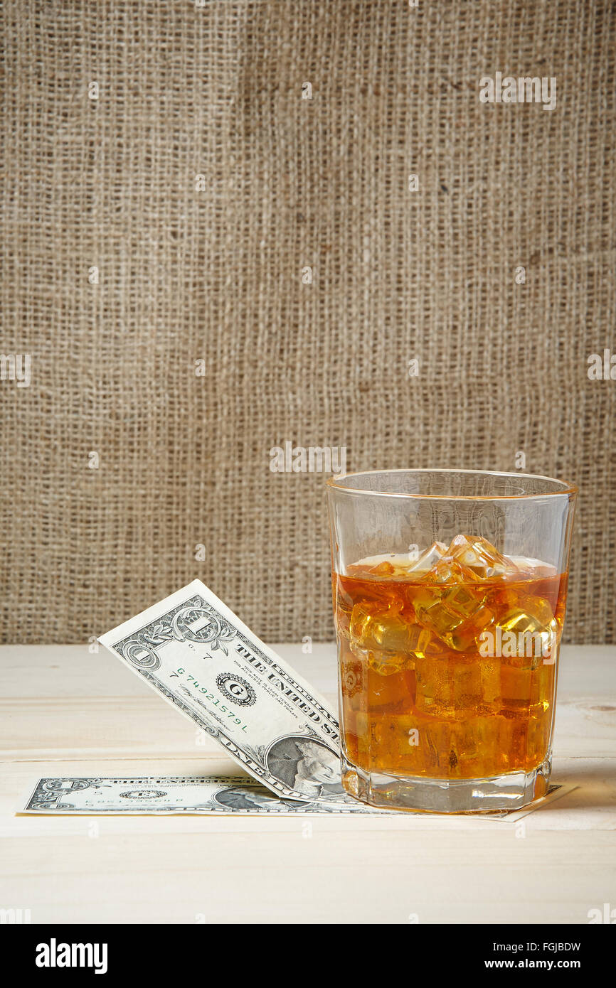 Dollars and glass of whiskey with ice on wooden table. Place for text - Stock Image